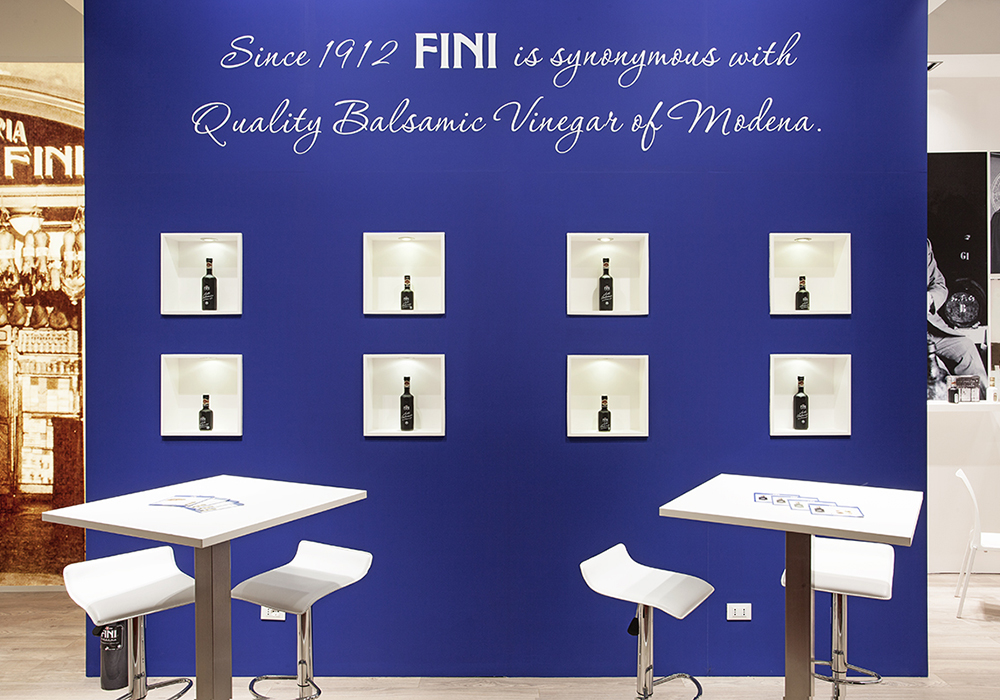 Postazioni con sedie e tavoli per clienti allo stand Fini