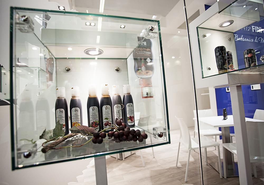 Vertrinetta con bottiglie di aceto in esposizione allo stand Acetaia Fini al salone Cibus 2014 alle fiere di Parma