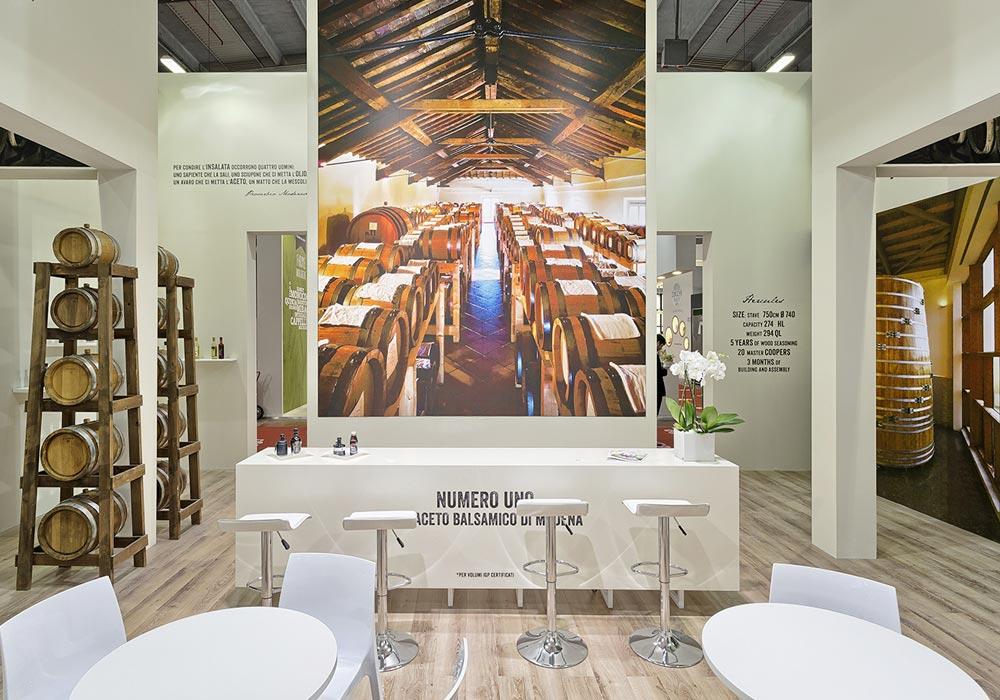 Bancone bianco e sgabelli nello stand dell'azienda Acetum allestito per il salone internazionale dell'alimentazione CIBUS che si tiene alla fiera di Parma.