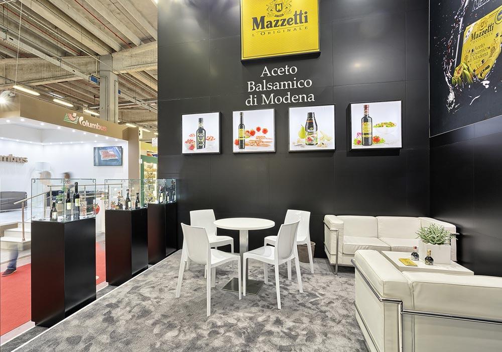 Salottino con divanetti e tavolini bianchi nello stand Mazzetti progettato per il Salone internazionale dell'alimentazione CIBUS tenutosi alle fiere di Parma.