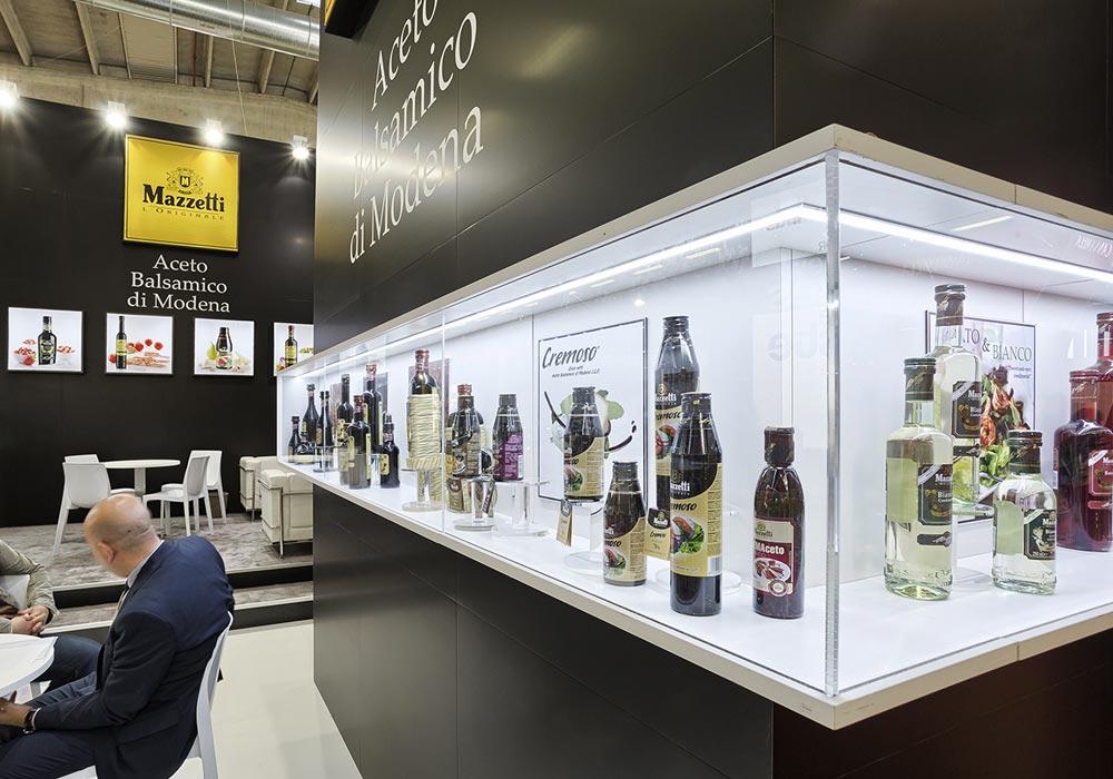 Lunga vetrina illuminata per esposizione prodotti allo stand Mazzetti progettato per il Salone internazionale dell'alimentazione CIBUS tenutosi alle fiere di Parma.